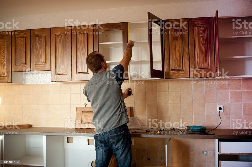 Man constructing cabinet units in new kitchen royalty-free stock photo