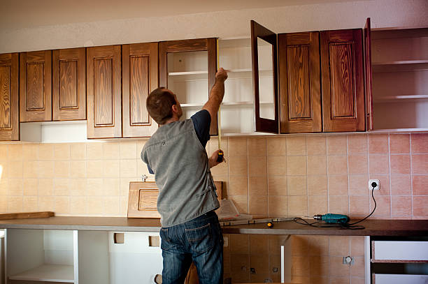 Man constructing cabinet units in new kitchen stock photo