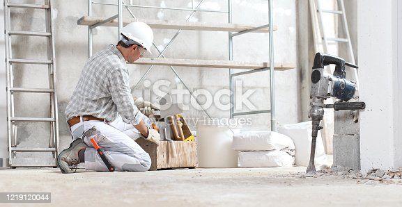 plasterer man construction worker work with tool box wear gloves, hard hat and protection glasses at interior building site with scaffolding. bucket, sacks and jackhammer