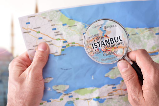 Man consulting a map of Istanbul with a magnifying glass