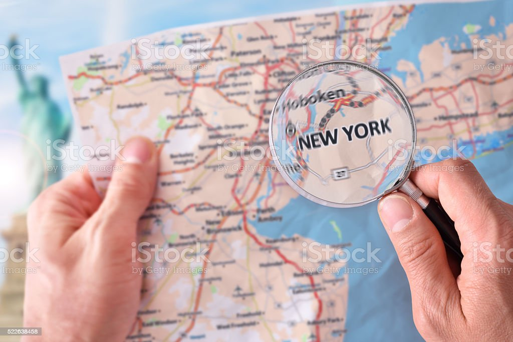 Man consulting a map of New York with magnifying glass stock photo