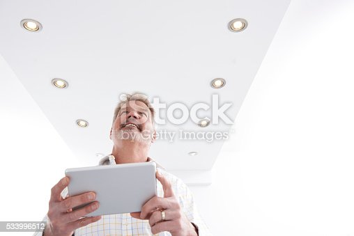 istock Man Controlling Lighting With App On Digital Tablet 533996512
