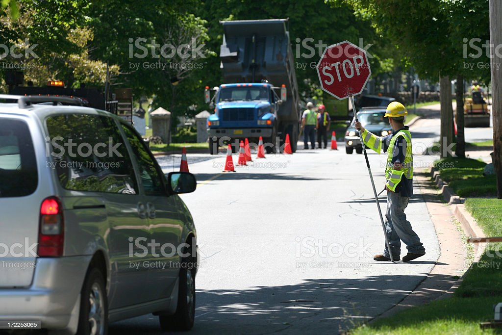 A man controlling traffic with a sign stock photo