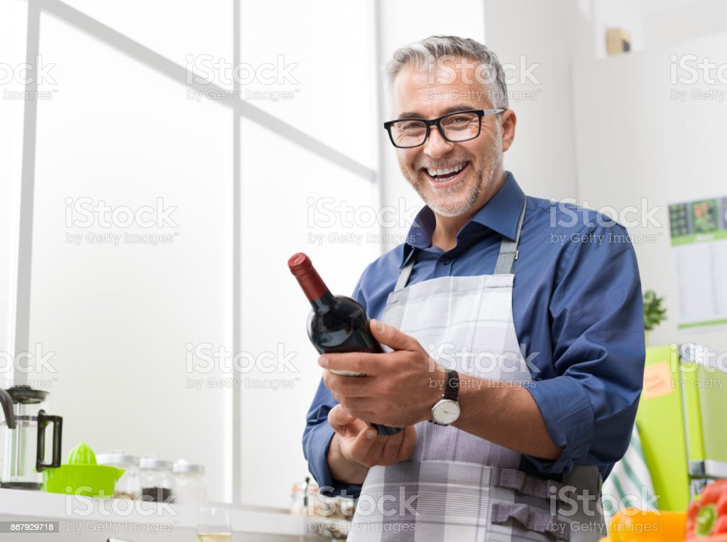 Mann, Kochen und hält eine Flasche Weine – Foto