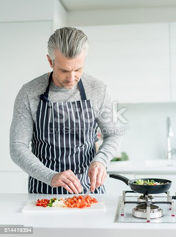 istock Man cooking dinner at home 514419394