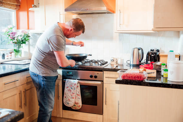 Man Cooking in his Kitchen Mature man is preparing a wok on the cooker to make spaghetti bolgnese at home. stay at home father stock pictures, royalty-free photos & images