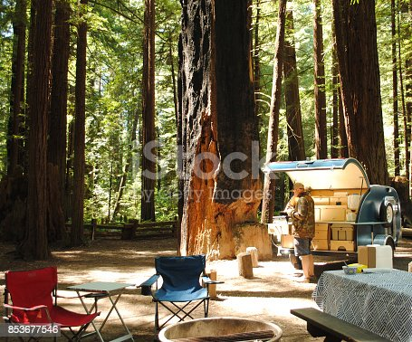 A man cooks over a propane stove in a teardrop trailer kitchen while camping surrounded by redwood trees in Humboldt Redwoods State Park in California