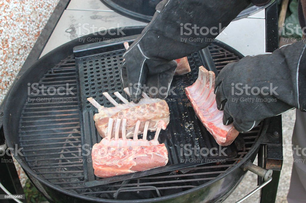 Man cooking large racks of ribs on the BBQ foto royalty-free
