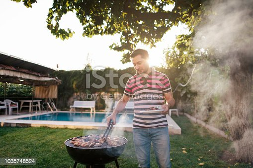 A mid adult man is cooking meat on bbq