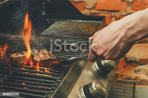 istock Man cooking meat steaks on professional grill outdoors 859632244