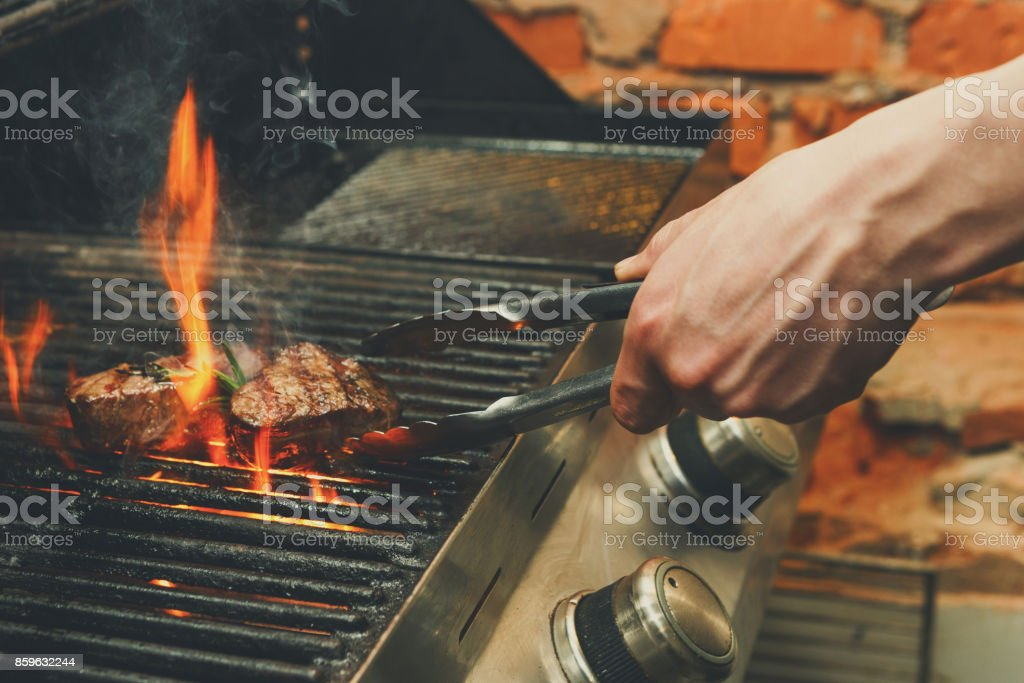 Man cooking meat steaks on professional grill outdoors stock photo