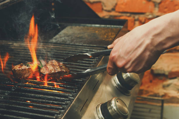 man cooking meat steaks on professional grill outdoors - barbecue grill stock photos and pictures