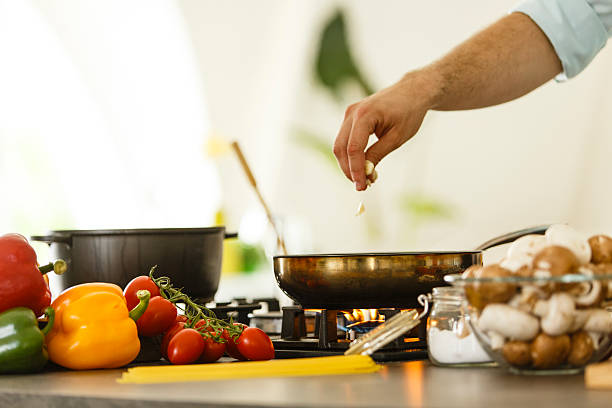 mann kochen - pilzpfanne stock-fotos und bilder