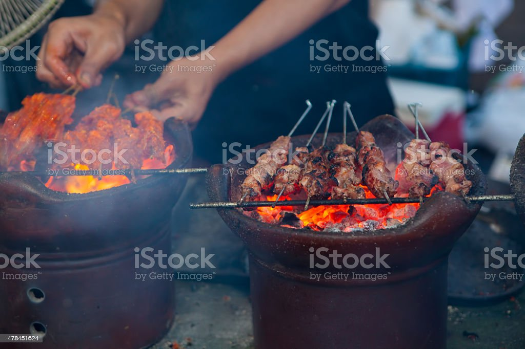 Man cooking satay klatak jogja on hot charcoal stock photo
