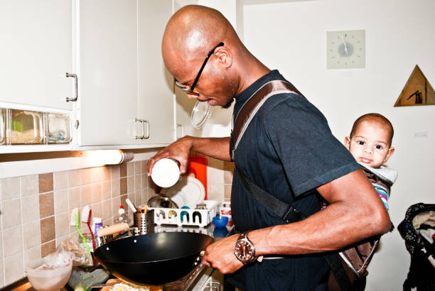 hombre de cocina mientras piggy forro un bebé - padre que se queda en casa fotografías e imágenes de stock