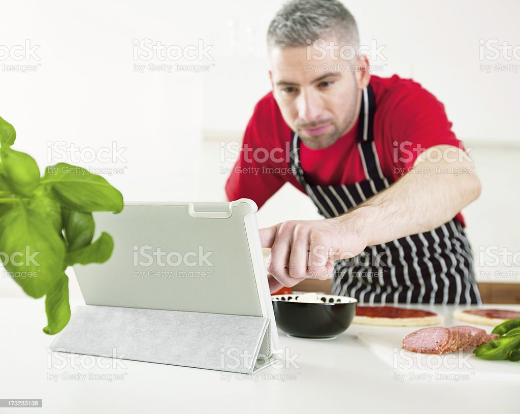 Man Cooking with Recipe from Digital Tablet royalty-free stock photo