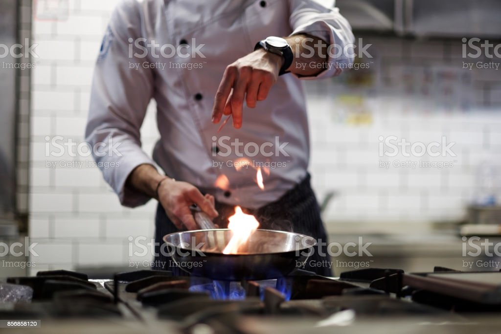 A man cooks cooking deep fryers in a kitchen fire. stock photo
