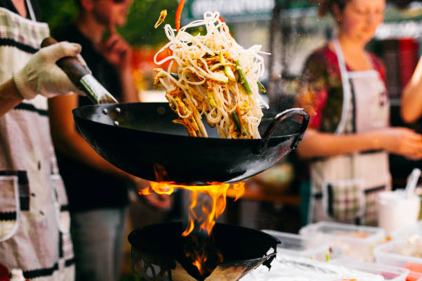 o homem cozinha macarronetes no incêndio - stir fry - fotografias e filmes do acervo