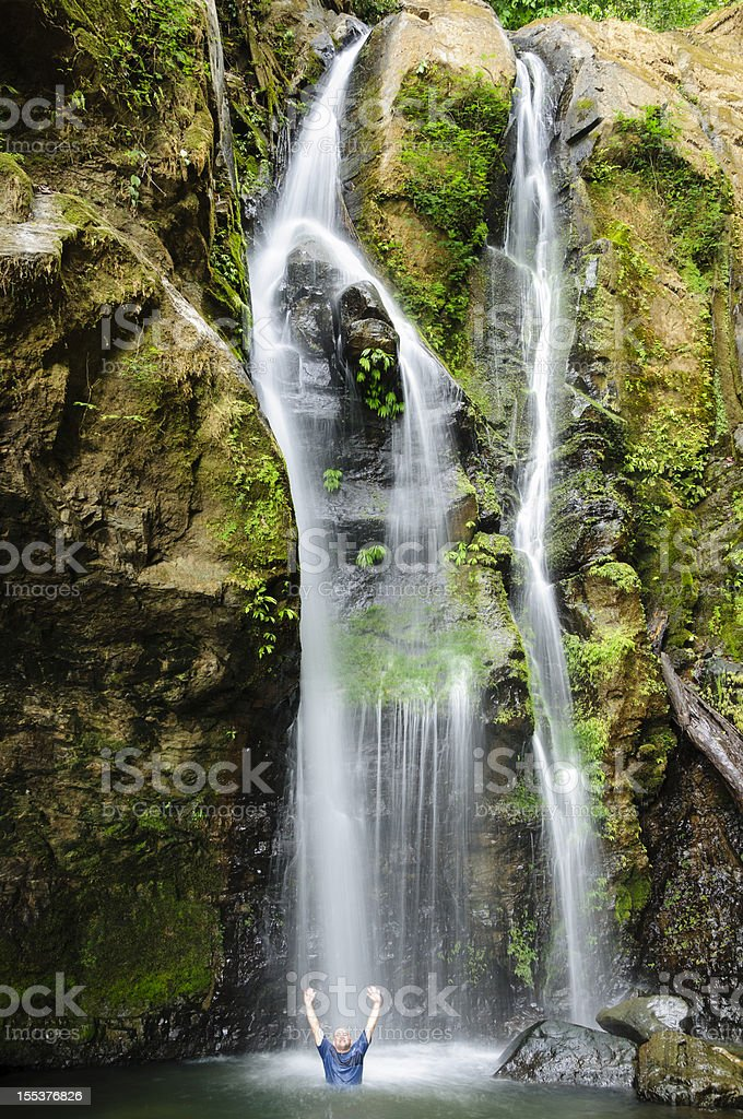 Man cooling down in a waterfall royalty-free stock photo