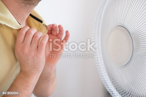 istock Man cooling in front of air electric fan 941800044