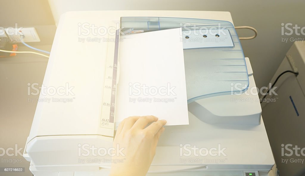 Man copying paper from Photocopier sunlight from window stock photo
