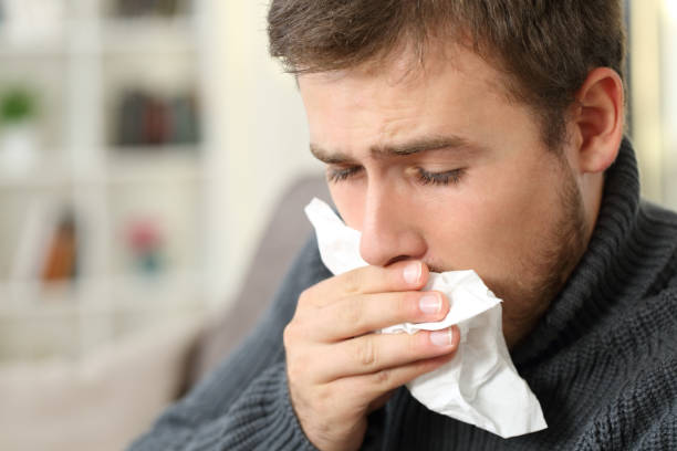 Man coughing covering mouth with a tissue at home Man coughing covering mouth with a tissue sitting on a couch in a house interior mucus stock pictures, royalty-free photos & images