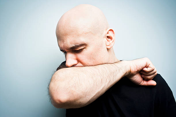 A man coughing into his arm on a blue background stock photo