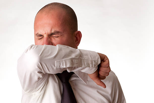 man coughing or sneezing into arm/elbow - sneezing bildbanksfoton och bilder