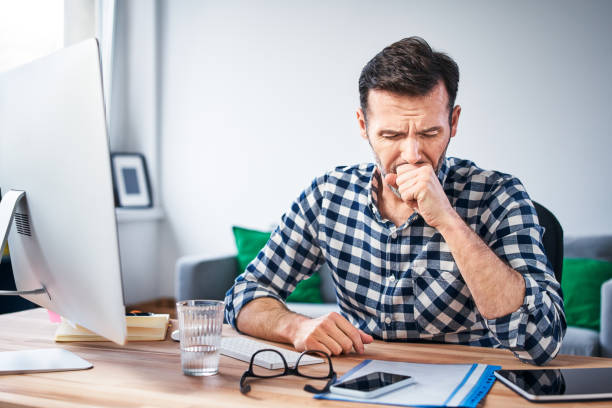 Man coughing while working on a computer from home stock photo