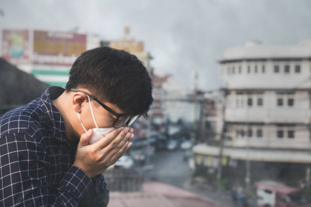 Man coughing.Man wearing face mask because of air pollution in the city