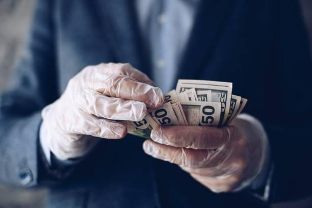 Mann zählt amerikanische Dollar-Geld-Banknoten in schützenden Latexhandschuhen. – Foto