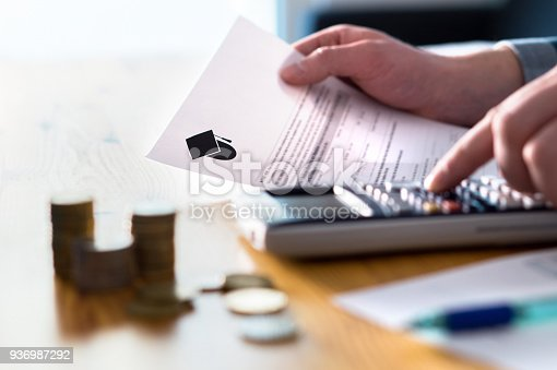 istock Man counting college savings fund, tuition fee or student loan with calculator. Education price and expenses concept. Money and papers on table. 936987292