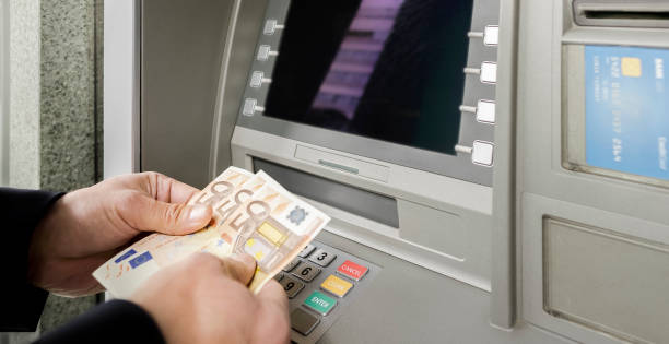 Man counting currency at ATM Businessman counting banknotes at cashpoint machine. fifty euro banknote stock pictures, royalty-free photos & images