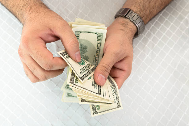man counting dollar notes - spending money stock pictures, royalty-free photos & images