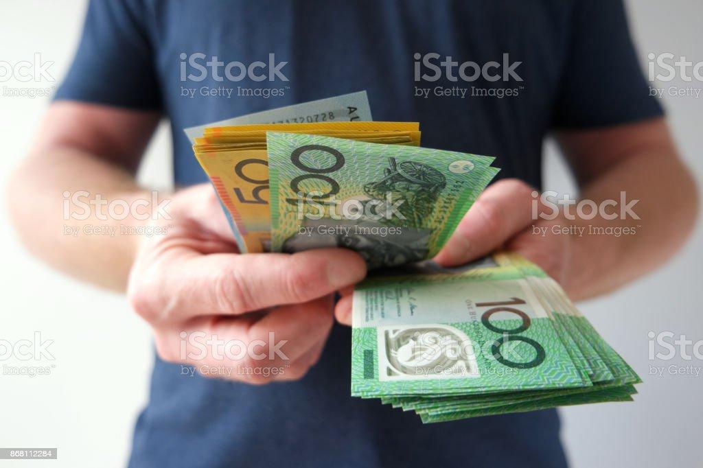Man counting hundreds and fifties Australian dollar bills stock photo