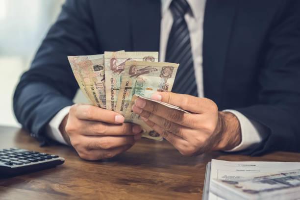 para, onun çalışma masasında bae dirhemi banknot sayma bir adam - bearn stok fotoğraflar ve resimler