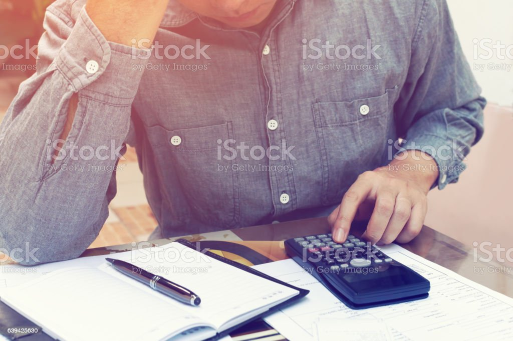 Man counting using calculator and stress in problem with expenses at...