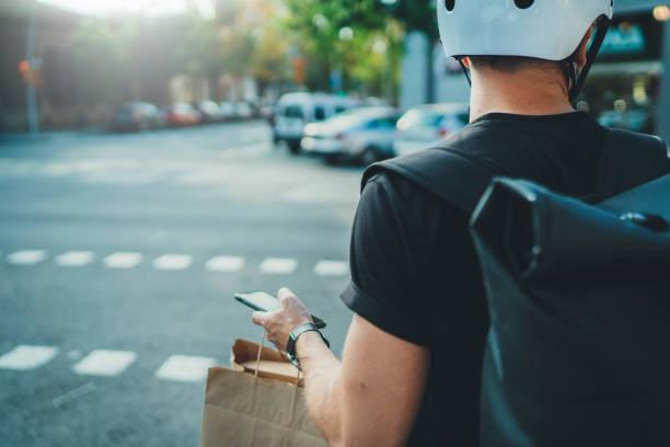 Mann Kurier mit einer Karte-App auf Handy, um die Lieferadresse in der Stadt zu finden. Anonimous Courier Delivery Food Service zu Hause. – Foto