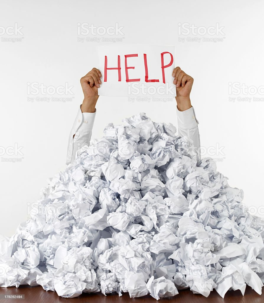 Man covered in wadded up paper holds a help sign above pile stock photo