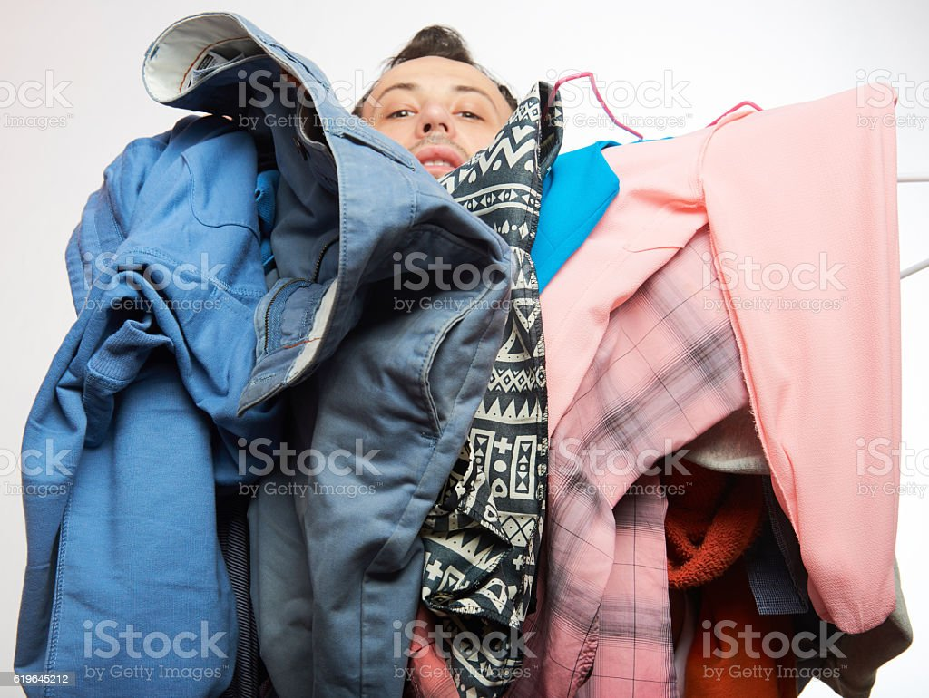 Man covered of stack clothes stock photo