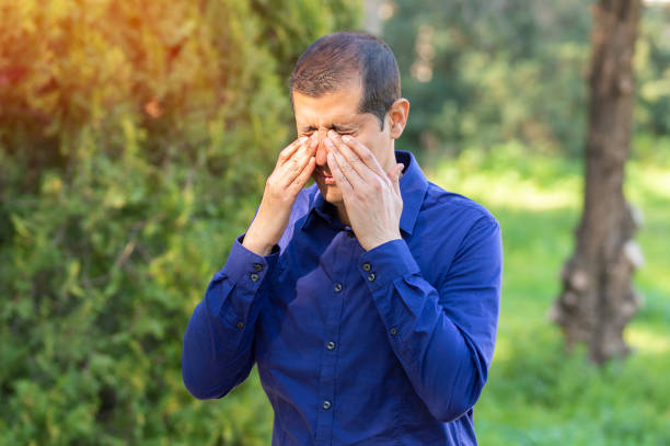 Man covering eyes by hands stock photo
