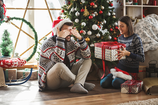Happy young couple celebrating Christmas together. The man is covering his eyes and waiting a present from his girlfriend.