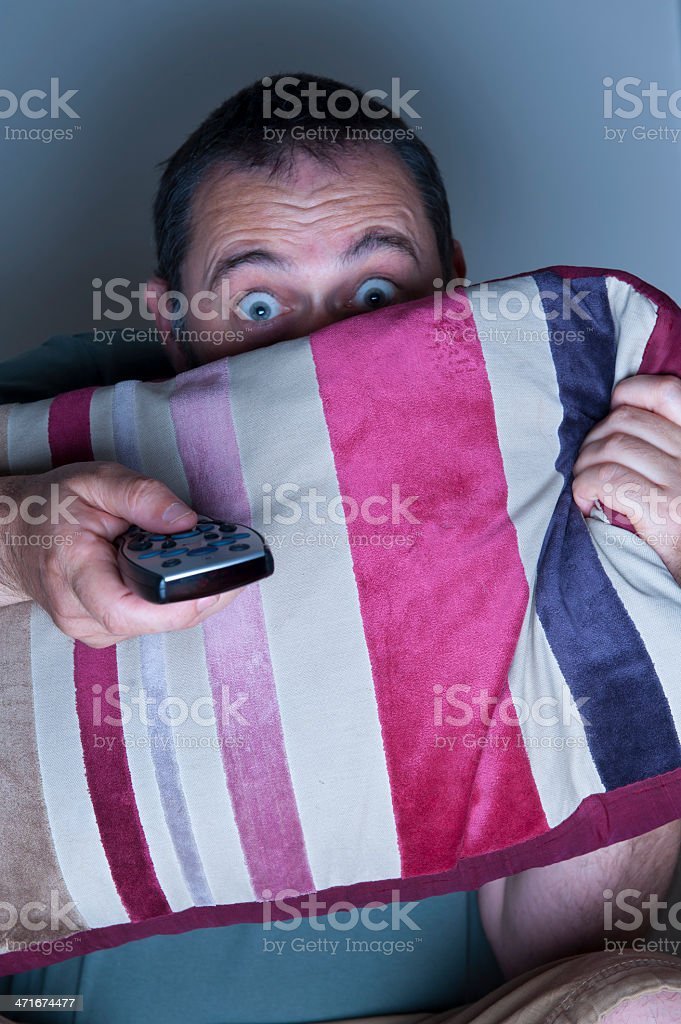 man covering face with a cushion watching tv royalty-free stock photo