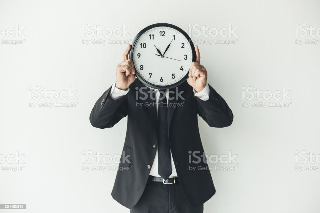 man covering face with clock on light background stock photo