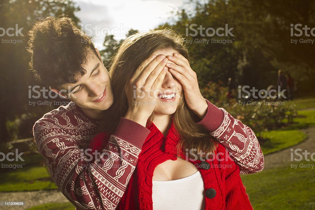 Man covering girlfriends eyes in park stock photo