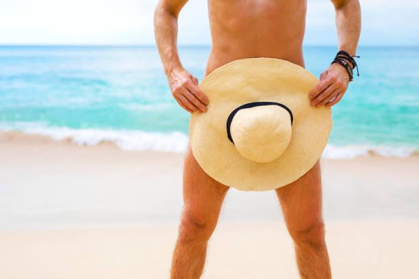 manndeckung selbst mit sommerhut - fkk strand stock-fotos und bilder