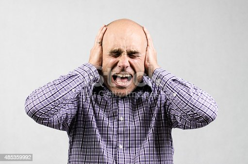 A man is covering his ears to protect them from noise in his head