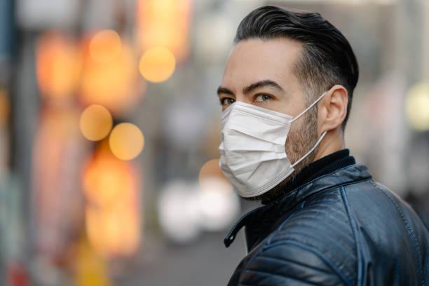 Man covering his face with pollution mask for protection from viruses A man is covering covering his mouth and nose with a pollution mask to protect himself from coronavirus, cold virus, flu virus, pollution. pollution mask stock pictures, royalty-free photos & images