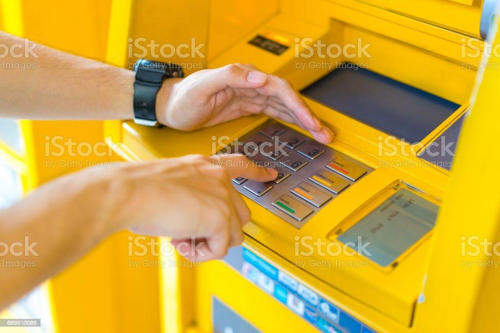 人の ATM で PIN を入力しながら彼の手をカバー ストックフォト
