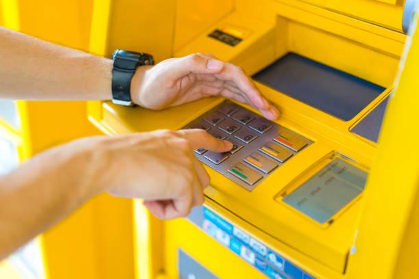 人の atm で pin を入力しながら彼の手をカバー - id盗難 ストックフォトと画像